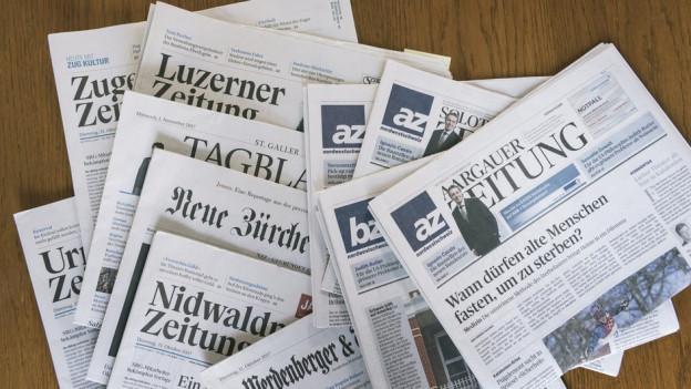 Zeitungen der AZ Medien und der NZZ Mediengruppe liegen auf einem Tisch.