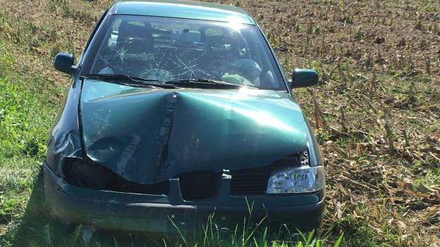 Beschädigtes Auto in einem Feld.