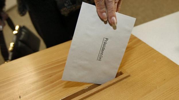 Frau legt Wahlzettel in die Urne