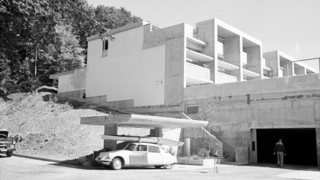 Beton-Reihenhaus mit Tankstelle und Auto, historische Aufnahme