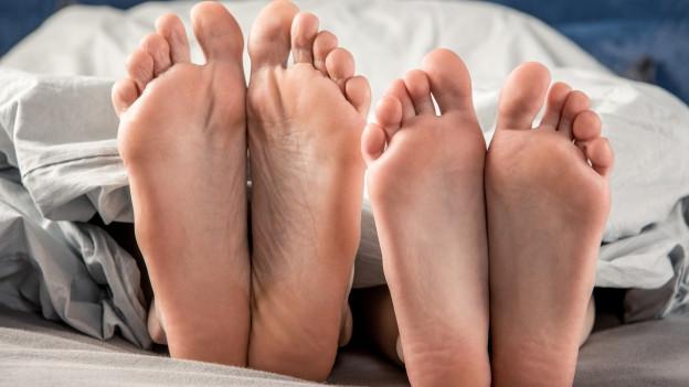 Füsse schauen unter Bettdecke hervor.