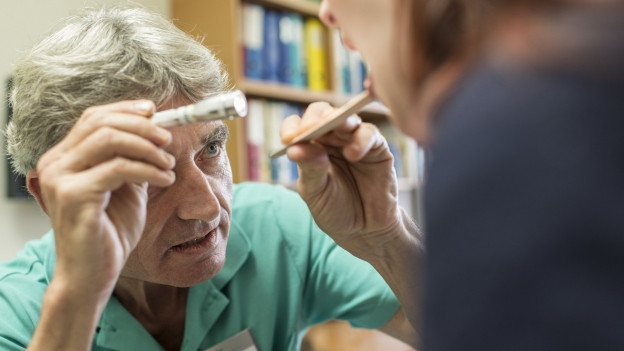 Älterer Arzt bei Untersuchung