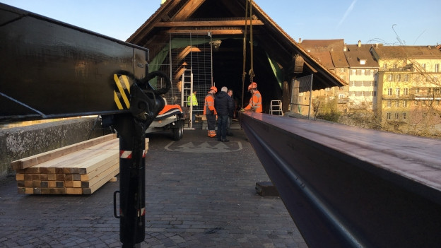 Die vom Feuer beschädigte Holzbrücke wird mit Stahlträgern verstärkt.