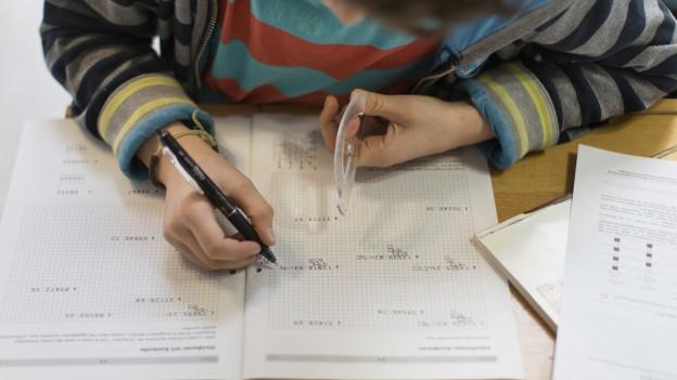 Ein Kind schreibt auf Papier.