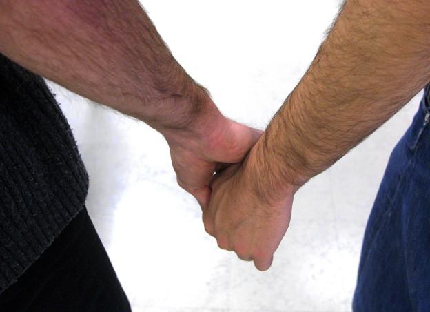 Zwei Männer halten einander die Hände.