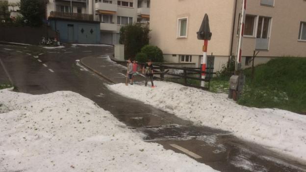 Kinder auf Bergen von Hagelkörnern.