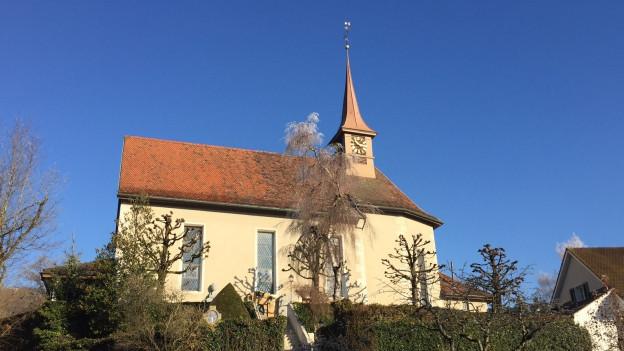 Gelbe Kirche mit braunem Dach.