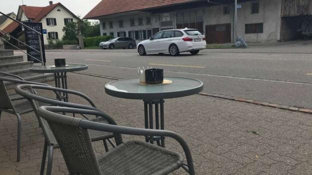 Tisch und Stühle an Strasse.