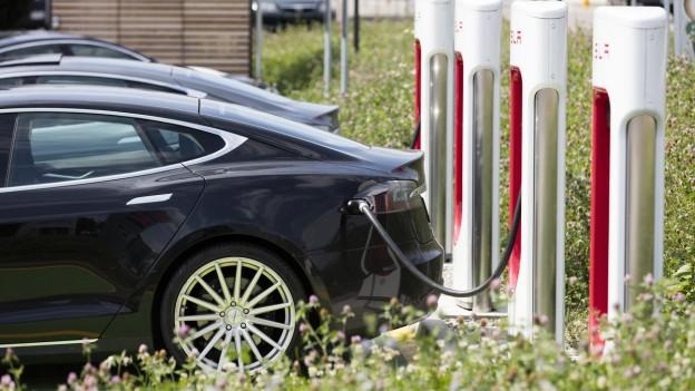 Ein Tesla tankt Strom an einer Strom-Tankstelle