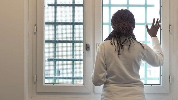 Frau schaut durch vergitterte Fenster