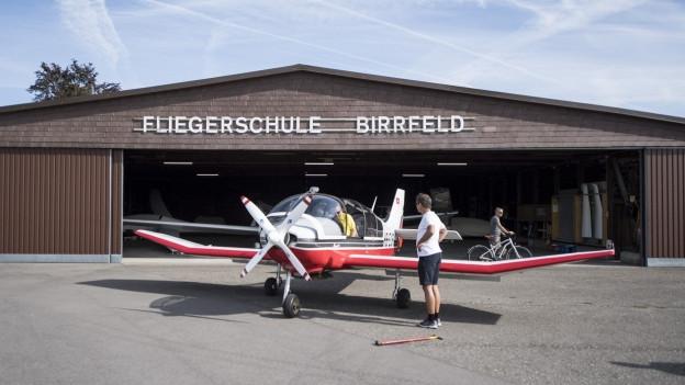 Kleines Flugzeug vor einem Hangar.