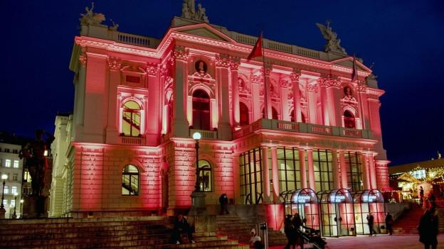 Rot beleuchtetes Opernhaus aus Stein.
