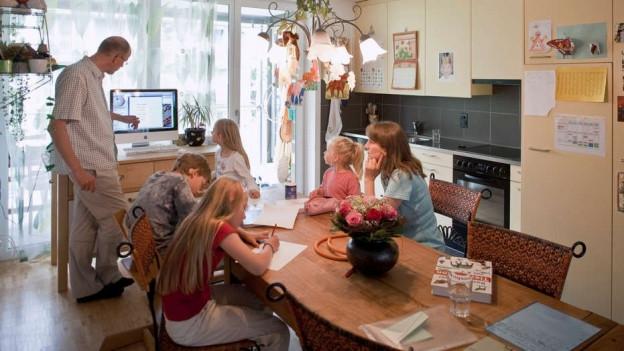 Frau unterrichtet Kind am Küchentisch