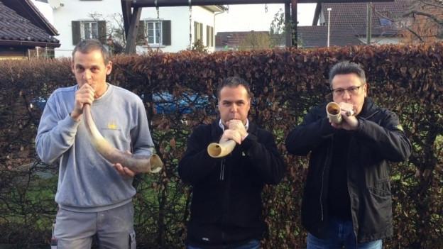 Drei Männer blasen in Hörner.