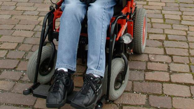 Die Beine eines Mannes im Rollstuhl