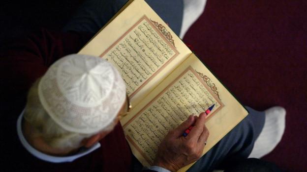 Mann liest in Buch mit arabischen Schriftzeichen.