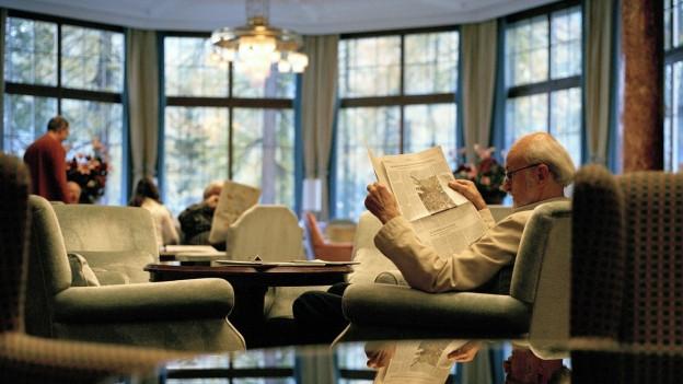 Ein Senior sitzt im Lehnstuhl und liest Zeitung