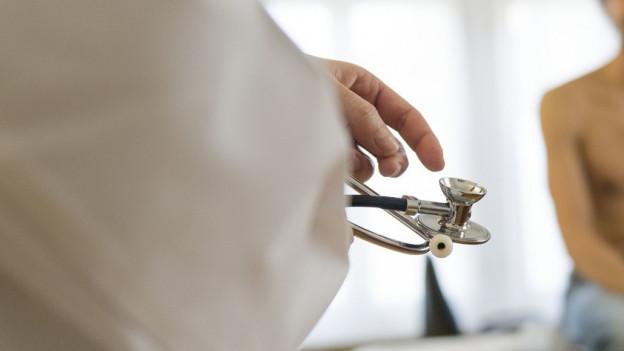 Ein Mann in einem weissen Kittel hält ein Stethoskop.