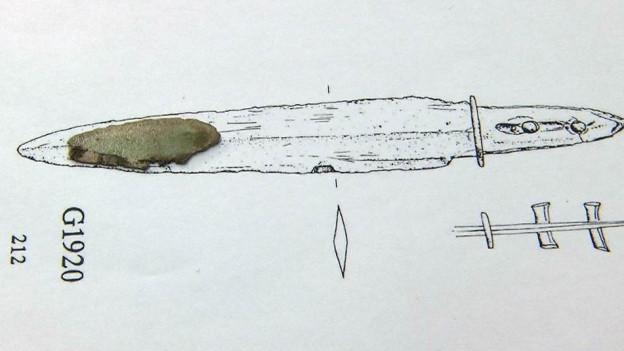 Ein Metallfragment auf der Skizze eines Dolches.