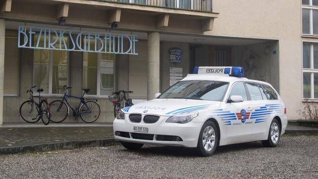Polizeiauto vor Gerichtsgebäude.