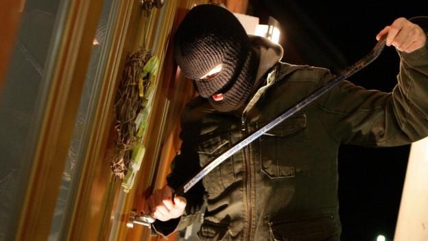 Ein Einbrecher macht sich an einer Tür zu schaffen.