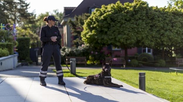 Sicherheitsdienst-Mitarbeiterin mit Hund.