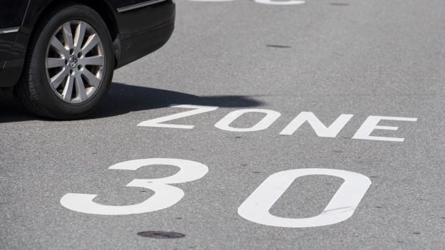 Beschriftung «Tempo 30» auf Strasse.