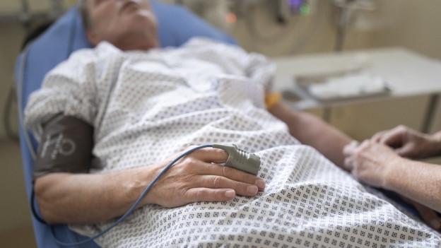 Mann liegt in einem Spitalbett