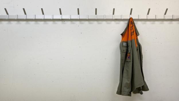 Zivilschutz-Jacke hängt an einem Garderoben-Haken