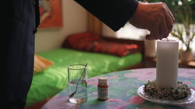 Männerhand zündet Kerze an, daneben liegt ein Medikament