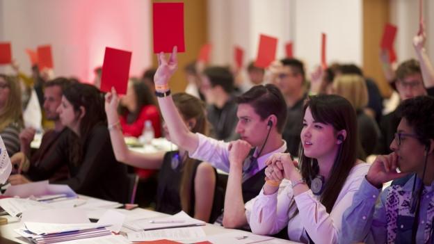 Jugendliche stimmen an einer Versammlung ab.