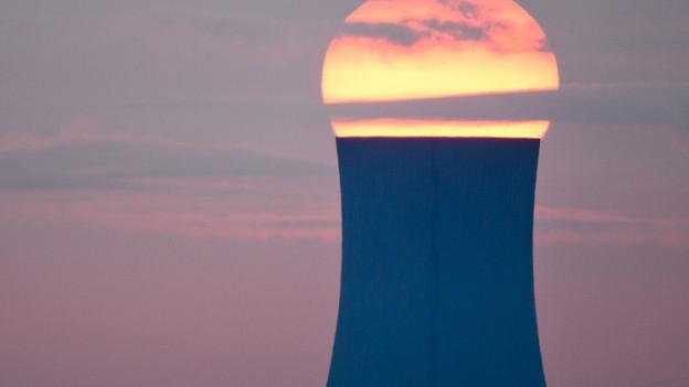 Die Sonne geht hinter einem Kohlekraftwerk unter.
