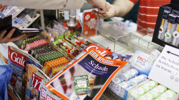 Eine Person kauft am Kiosk ein Nachrichtenmagazin.