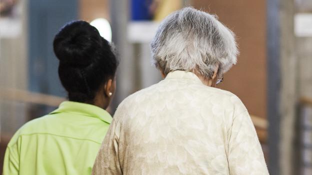 Eine junge Betreuerin begleitet eine ältere Frau.