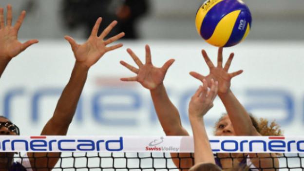 Volleyball-Spielerinnen am Netz.