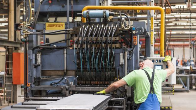 Ein Mann in einer Fabrikhalle.