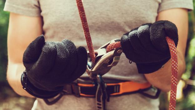 Handschuhe halten ein Seil.