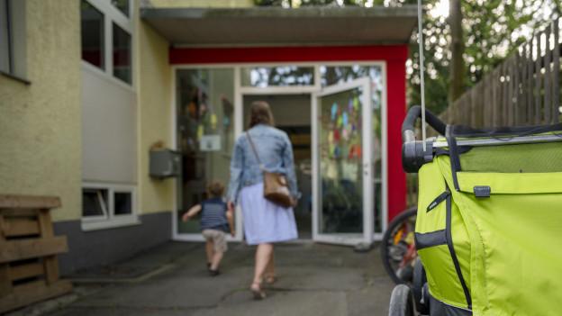 Frau und Kind gehen auf offene Türe zu.