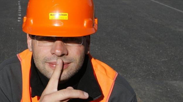 """Ein Strassenarbeiter steht auf einer Baustelle und macht """"Pssst""""."""