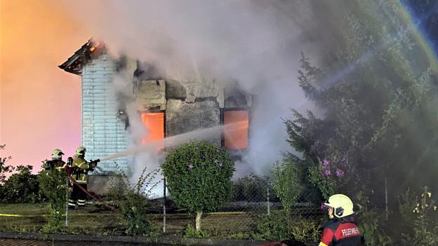 Feuerwehrmänner löschen ein stark brennendes Haus
