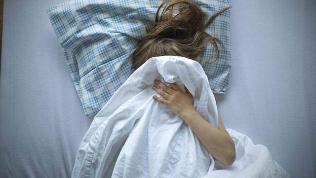 Mädchen im Bett mit Decke über dem Kopf.