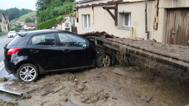 Auto unter Schlamm und Trümmern.