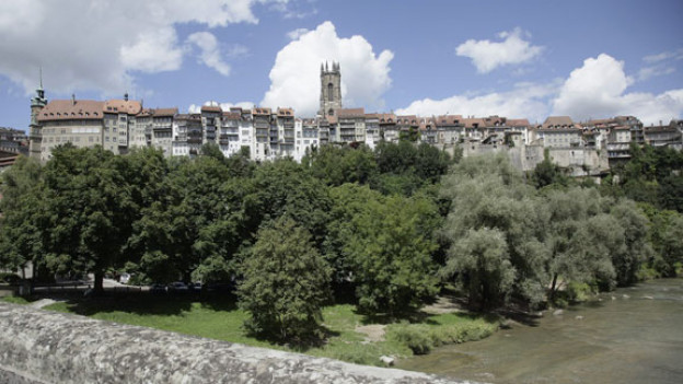 Blick auf eine Häuserfront mit Kirchturm.