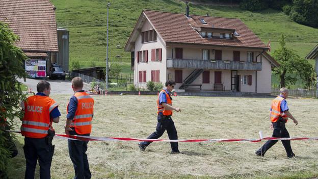 Polizisten bewachten im Mai 2011 das Haus in Schafhausen, in dem ein Polizist erschossen wurde.