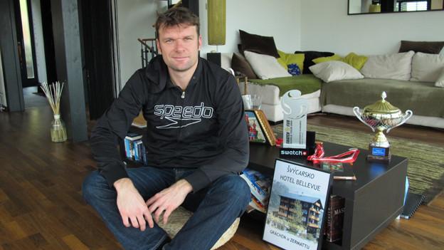 Martin Laciga in seinem Wohnzimmer in Kerzers - mit Pokalen und dem Bild des Familienhotels in Grächen.