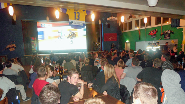 Gottéron-Fans schauen sich das Spiel in Düdingen auf Grossleinwand an.