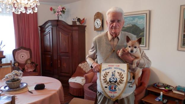 Josef Markwalder mit seinem Hund Lucki und einem Wimpel der 50-Jahr-Feier Gottérons.
