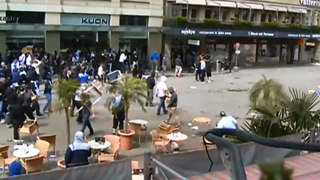 Fans werfen in der Innenstadt mit Tischen und Stühlen.