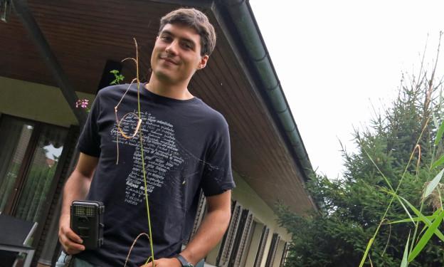 Thierry Aebischer mit einer Fotofalle im Garten seiner Eltern.