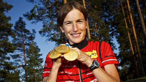 Simone Niggli posiert bei der WM 2013 in Vuokatti mit ihren Goldmedaillen.